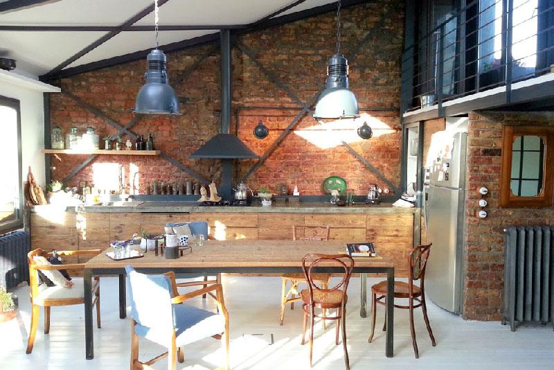 cuisine dans un loft de style rustique et industriel. On aime les lampes bleu et la présence de briques