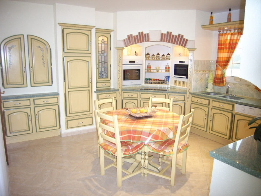 Ici, on retrouve tout ce qui fait le charme de la cuisine e Provence : couleurs ensoleillées, moulures et petits dessins sur les meubles, décoration murale et même les nappes de couleurs vives!