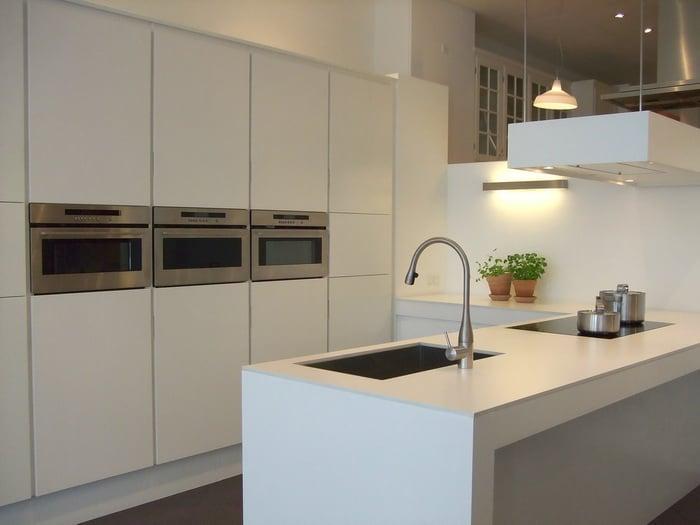 aménagement d'une petite cuisine design blanche avec équipement inox et évier sous plan