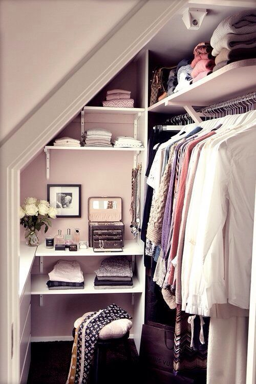 Dressing dans des combles en blanc avec étagères contenant des draps ...